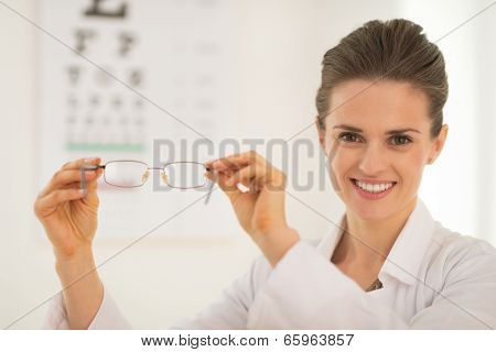 Ophthalmologist Doctor Woman Showing Eyeglasses In Front Of Snel