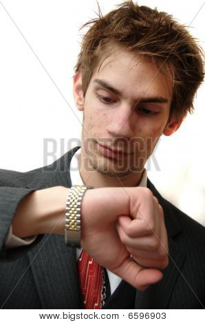 Attractive Young Businessman In Suit Checks His Golden Wrist Watch For The Time