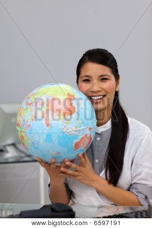 Confident Asian Businesswoman Holding Terrestrial Globe