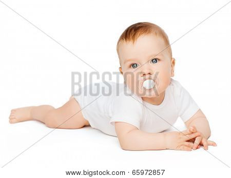 child and toddler concept - smiling baby lying on floor with dummy in mouth