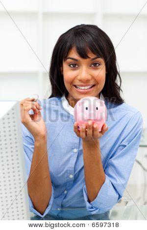 Smiling Businesswoman Saving Money In A Piggybank