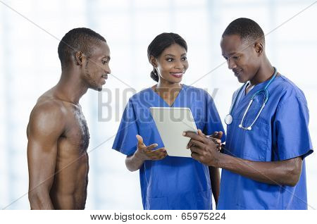 African Health Care Team With Tablet Pc And Patient