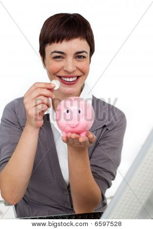 Joyful Female Executive Saving Money In A Piggybank
