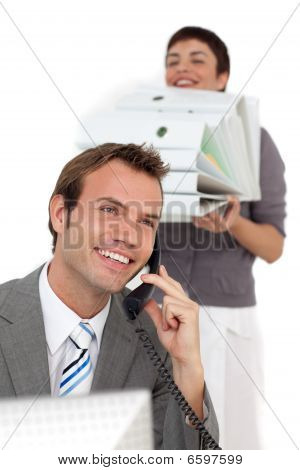 Businessman On Phone With His Colleague Bringing A Stack Of Folders