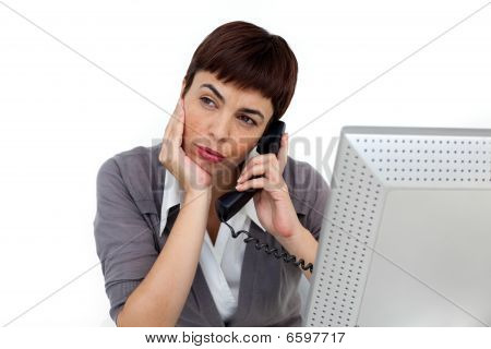 Young Businesswoman On Phone At Her Desk