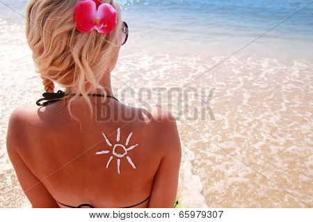 Of Sun Cream On The Female Back On The Beach