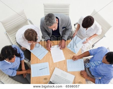 Concentrated International Business People Studying A Contract