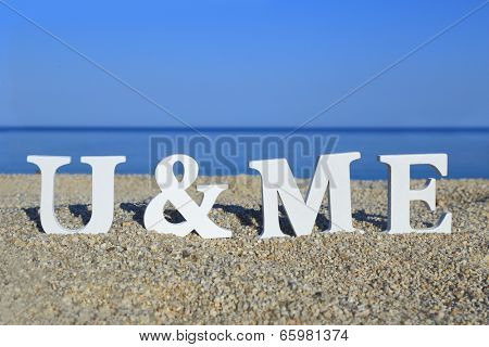 Seascape with white words you and me on the sand