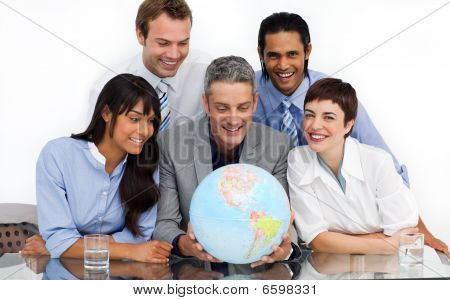 A Business Group Showing Diversity Looking At A Terrestrial Globe
