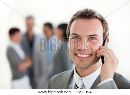 Young Businessman On Phone In Front Of His Team
