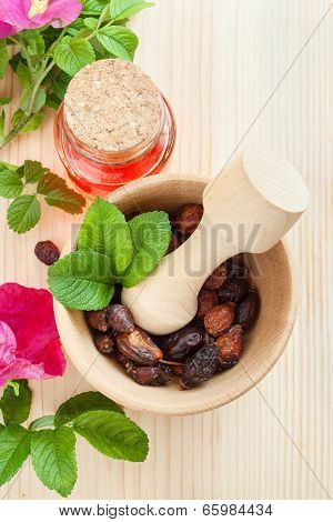 Essential Oil In Glass Bottle, Dried Rose-hip Berries In Wooden Mortar And Rose Hip Flowers, Top Vie