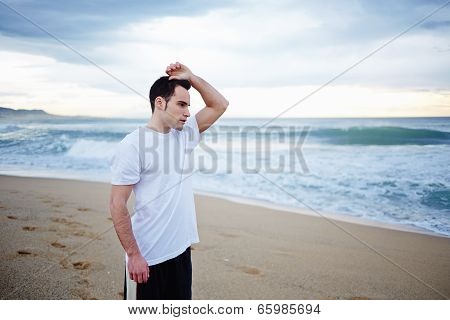 Beautiful athletic man resting on the beach after the jogging