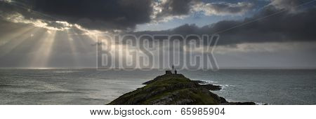 Landscape Panorama Of Mumbles Lighthouse In Wales With Sunbeams Over Sea