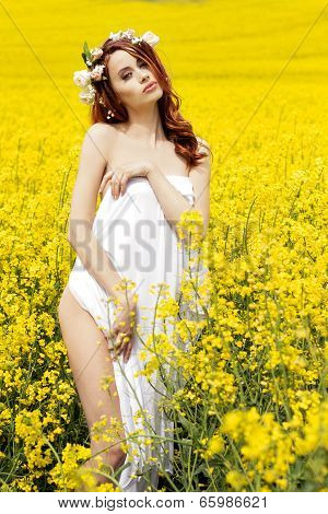 Young attractive sexy girl on a sunny day of flowering rape field with flowers in red hair