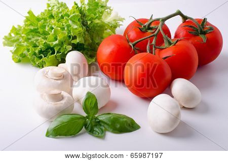 White Champignons Ripe Tomatoes On A Branch And Leaves Of Lettuce, Basil On A White Table