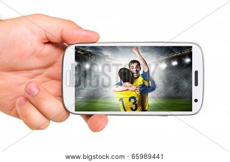 hand is holding a modern phone with soccer or football player on screen