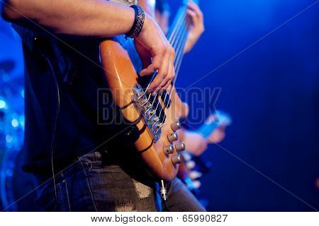 young man playing bass live. Body.