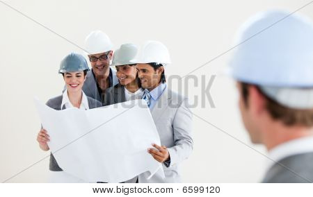 Male Engineer Looking Back At His Smiling Colleagues