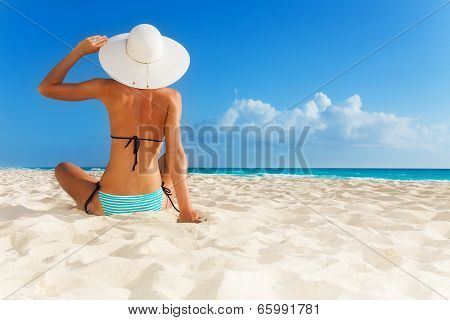 Tanned Young Girl Sitting On The Beach