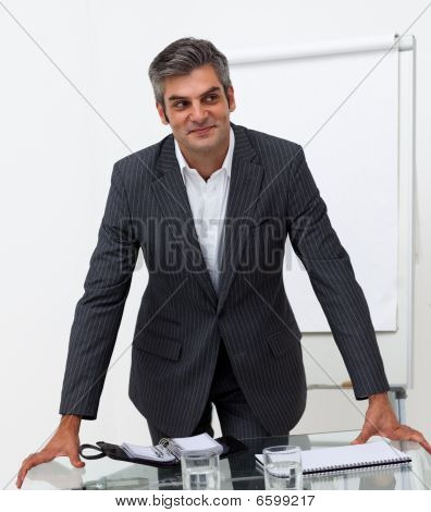 Smiling Mature Businessman Leaning On A Conference Table