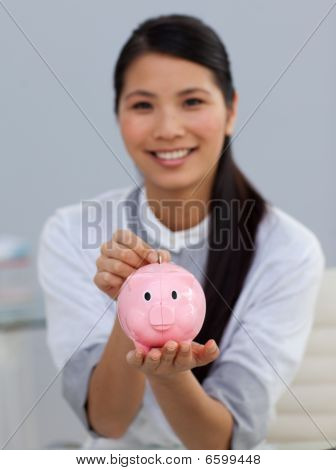 Young Ethnic Businesswoman Saving Money In A Piggybank