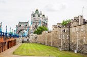 stock photo of fortified wall  - View of wall the Tower of London with Tower Bridge in the background - JPG