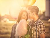 foto of candy cotton  - smiling  young  couple in love with cotton candy in amusement park - JPG