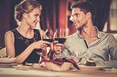 stock photo of restaurant  - Beautiful young couple with glasses of red wine in luxury restaurant - JPG