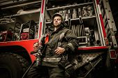 stock photo of firefighter  - Firefighter near truck with equipment with water water hose over shoulder - JPG