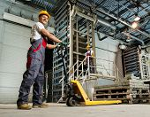 pic of heavy equipment operator  - Young worker moving paving stones with pallet truck on a factory - JPG