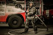 stock photo of fire-station  - Firefighter holding water hose near truck with equipment - JPG