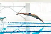 pic of goggles  - Young muscular swimmer jumping from starting block in a swimming pool - JPG