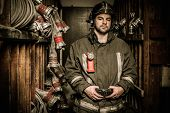 pic of firefighter  - Firefighter in storage room with fire hoses - JPG