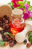 stock photo of wild-brier  - essential oil in glass bottle dried rose - JPG