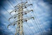 stock photo of hydro  - Looking up at a towering electric hydro transmission tower standing against a cloudy blue sky - JPG
