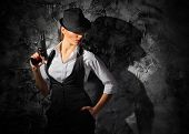 picture of gun shot  - Woman with gun on grey wall background - JPG