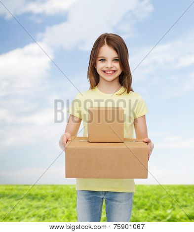 advertising, childhood, delivery, mail and people - smiling little girl holding cardboard boxes over natural background