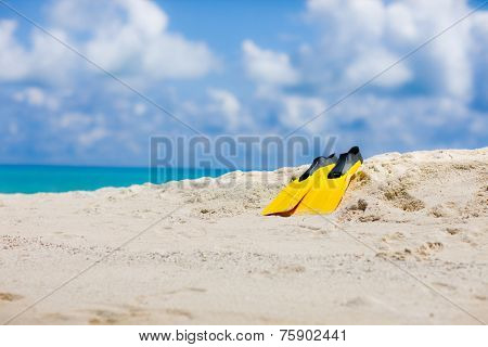 Yellow flippers on Maldivian beach in the Indian ocean