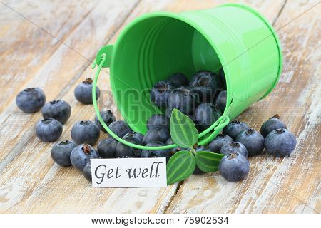 Get well card with blueberries scattered on wooden surface