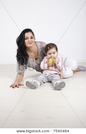 Smiling Mother And Baby Girl Sitting On Floor