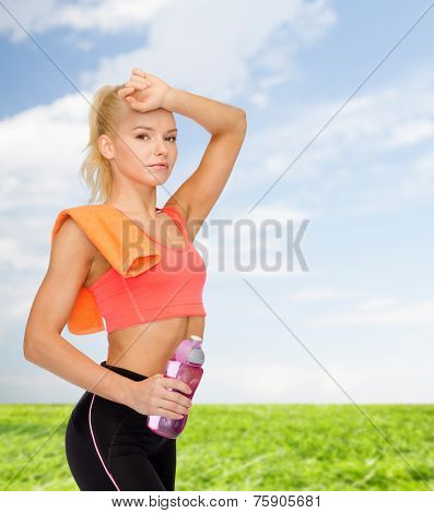 sport, exercise and healthcare concept - tired sporty woman with orange towel and water bottle