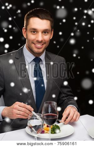 food, people, technology and holidays concept - smiling man with tablet pc eating main course at restaurant over black snowy background