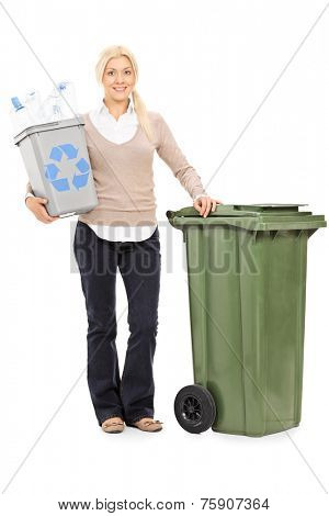 Full length portrait of a woman holding a recycle bin and standing by a large trash can isolated on white background