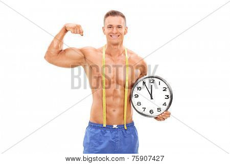 Handsome male athlete holding a big wall clock and flexing his muscle isolated on white background