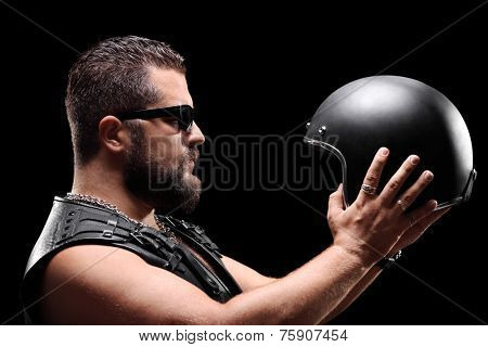 Biker holding a helmet on black background
