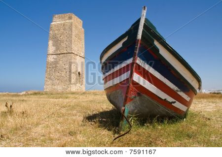 Wooden fishing boat and stone tower