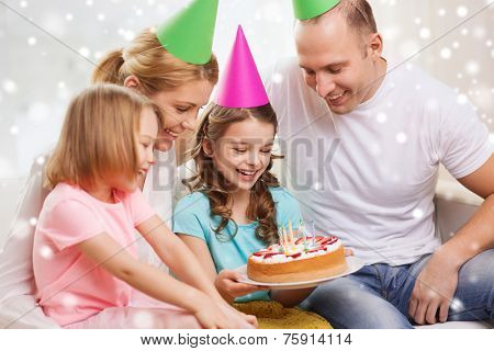celebration, family, holidays and people concept - happy family with two kids in party hats at home