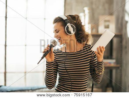 Happy Young Woman Singing Karaoke In Loft Apartment