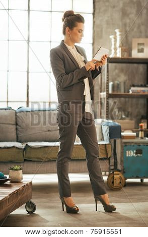 Full Length Portrait Of Business Woman Using Tablet Pc In Loft A
