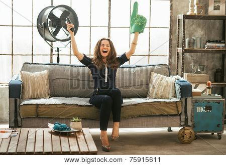 Portrait Of Football Fan Woman Watching Tv In Loft Apartment And